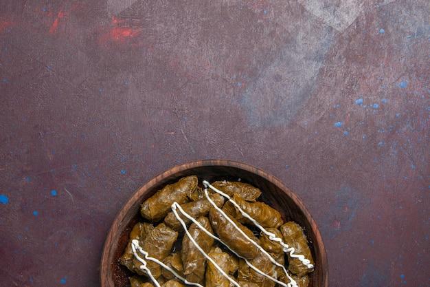 Vista superior del delicioso plato oriental de dolma con hojas y carne molida en el interior sobre fondo oscuro plato de aceite de comida de carne de cena de calorías