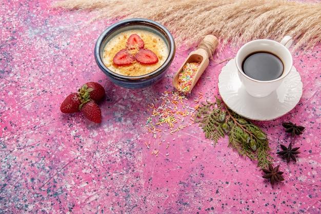 Vista superior delicioso postre cremoso con fresas en rodajas rojas y una taza de té en el fondo rosa claro postre helado baya crema fruta dulce