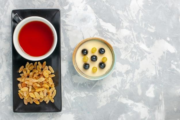 Vista superior delicioso postre cremoso con taza de té y pasas en superficie blanca postre crema de frutas helado helado dulce