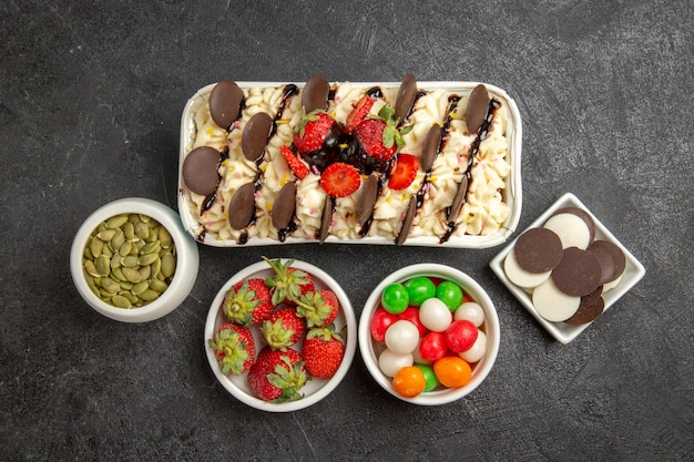 Vista superior delicioso postre con galletas y caramelos sobre fondo oscuro nuez galleta fruta dulce galletas azúcar