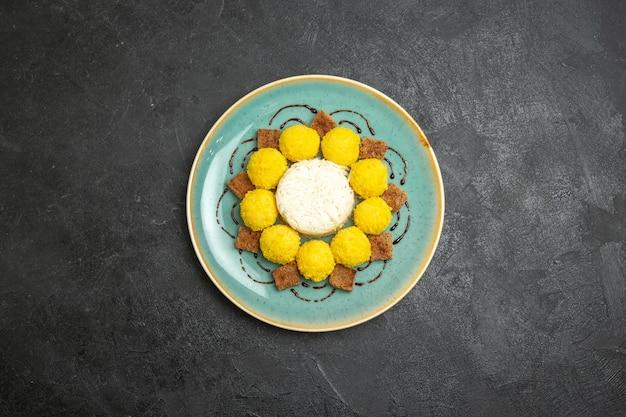 Vista superior del delicioso postre pequeños caramelos amarillos con pastel dentro de la placa sobre el fondo gris dulce té azúcar pastel dulce