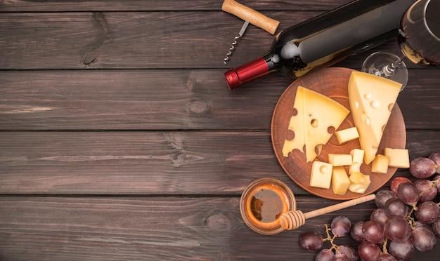 Vista superior delicioso queso con botella de vino y uvas