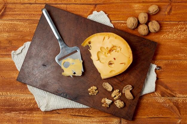Vista superior delicioso queso sobre una plancha de madera