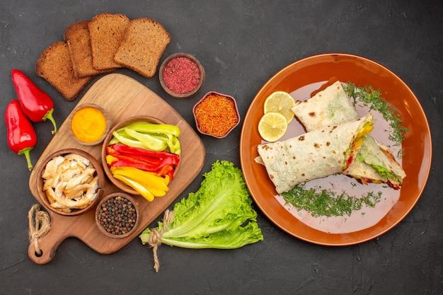 Vista superior del delicioso sándwich de ensalada shaurma en rodajas con panes de pan oscuro en la oscuridad