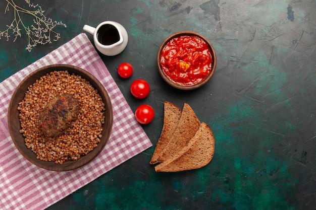 Vista superior delicioso trigo sarraceno cocido con chuleta y pan oscuro en el plato de verduras de comida de ingrediente de superficie verde oscuro