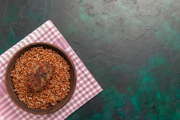 Vista superior delicioso trigo sarraceno cocido con chuleta en plato de verduras de comida de ingrediente de superficie verde oscuro