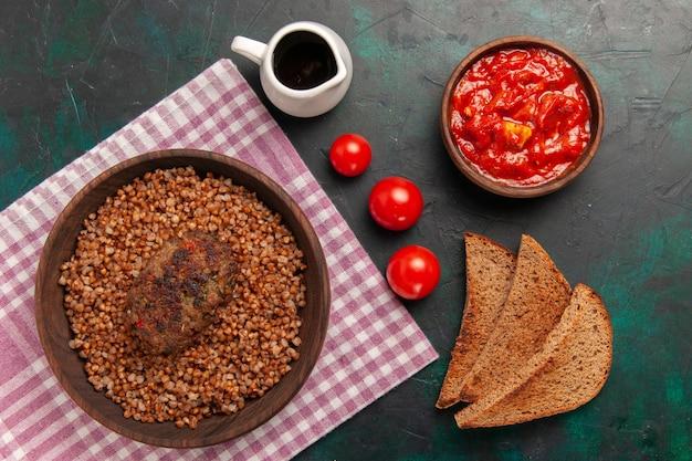 Vista superior delicioso trigo sarraceno cocido con chuletas y hogazas de pan en el plato de verduras de comida de ingrediente de superficie verde oscuro