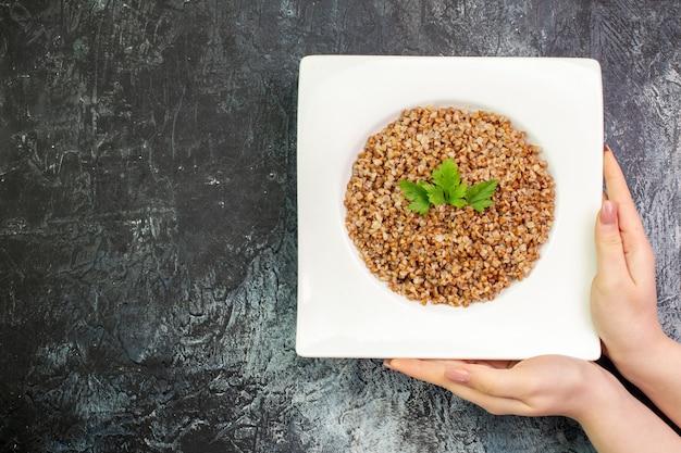 Vista superior delicioso trigo sarraceno cocido dentro de la placa sobre fondo gris claro comida calórica comida foto en color frijol