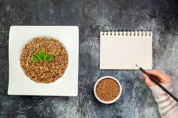 Vista superior delicioso trigo sarraceno cocido dentro de la placa sobre el fondo gris claro comida calórica foto en color plato comida frijol