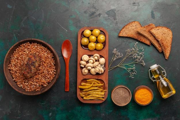 Vista superior del delicioso trigo sarraceno cocido con diferentes condimentos y pan en un plato de verduras de comida de ingrediente de superficie verde oscuro