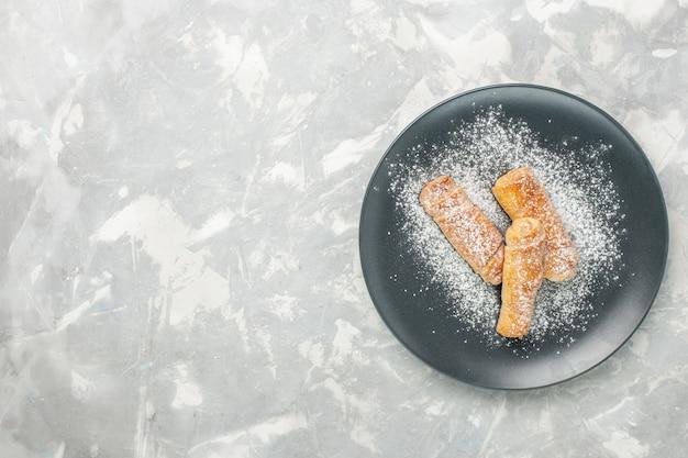 Vista superior de deliciosos bagels dulces azúcar en polvo sobre superficie blanca