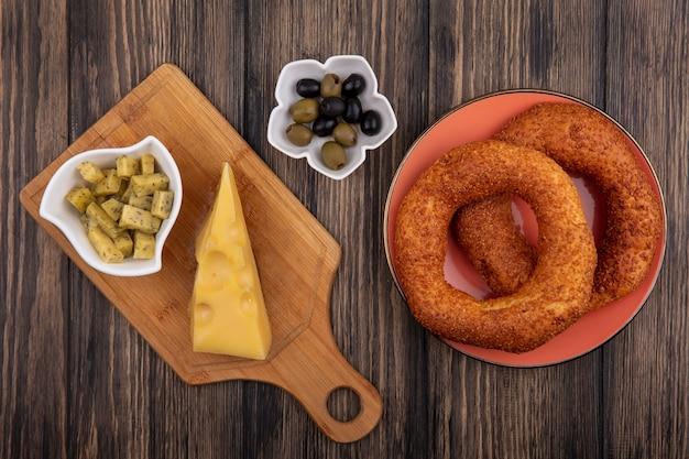 Vista superior de deliciosos bagels de sésamo turco en un plato con aceitunas en un recipiente con queso sobre una tabla de cocina de madera sobre un fondo de madera