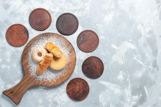 Vista superior deliciosos bagels con tortas en el escritorio de color blanco claro.