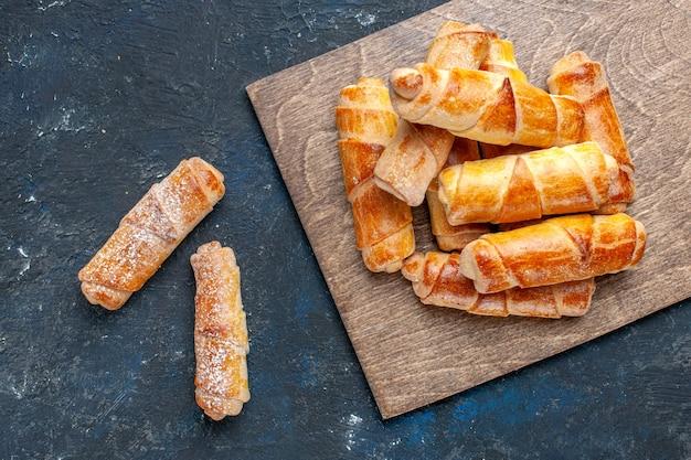 Vista superior de deliciosos brazaletes dulces con relleno delicioso horneado en oscuro, hornear pastel galleta postre dulce de azúcar