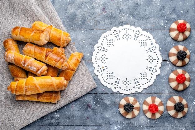 Vista superior deliciosos brazaletes con relleno junto con galletas en el fondo gris pastel hornear galleta dulce