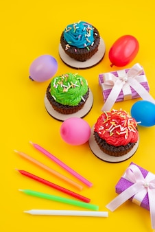 Una vista superior de deliciosos brownies a base de chocolate junto con caramelos y bolas en amarillo, color de galleta de pastel de caramelo