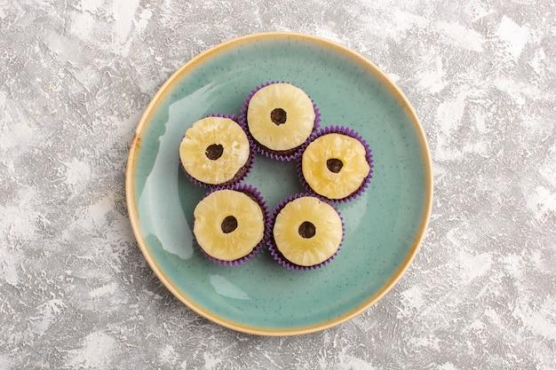 Vista superior de deliciosos brownies de chocolate dentro de la placa verde con anillos de piña en el fondo claro pastel de azúcar hornear masa dulce