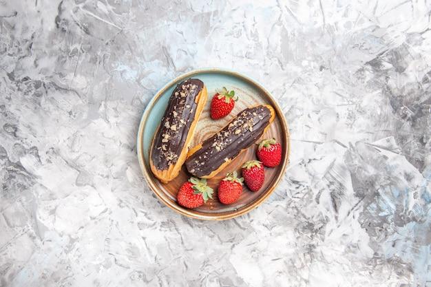 Vista superior deliciosos canutillos de chocolate con fresas en frutas de pastel de postre ligero