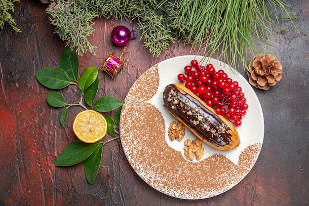 Vista superior deliciosos canutillos de chocolate con frutos rojos en la mesa oscura pastel postre dulce