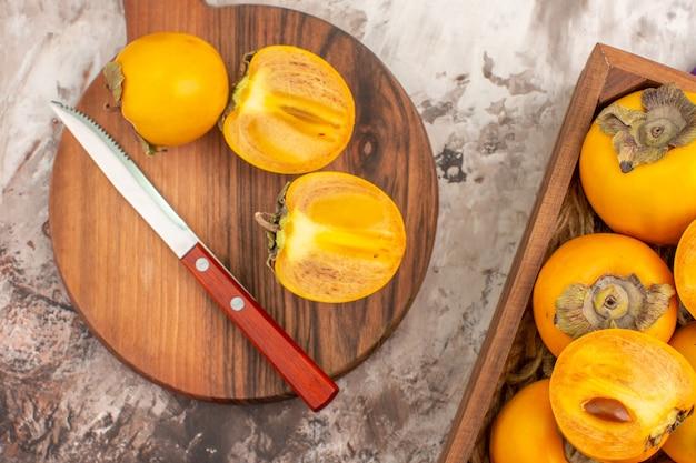 Vista superior deliciosos caquis un cuchillo en la caja de caquis de tabla de cortar sobre fondo desnudo