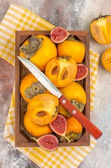 Vista superior de deliciosos caquis e higos cortados en caja de madera amarilla una toalla de cocina sobre fondo desnudo