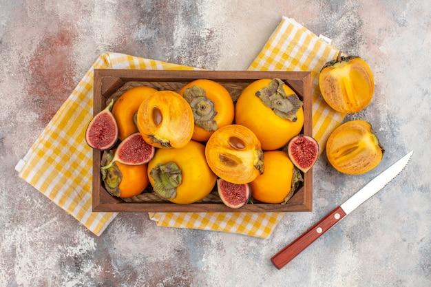 Vista superior deliciosos caquis e higos cortados en caja de madera un caqui cortado un cuchillo sobre fondo desnudo