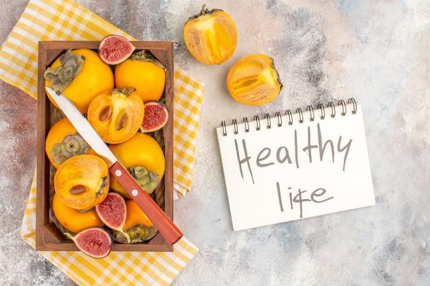 Vista superior deliciosos caquis e higos cortados en caja de madera toalla de cocina amarilla vida sana escrita en el cuaderno