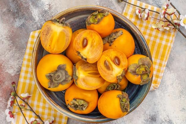 Vista superior deliciosos caquis en un tazón de fuente amarillo toalla de cocina rama de flor de albaricoque sobre fondo desnudo