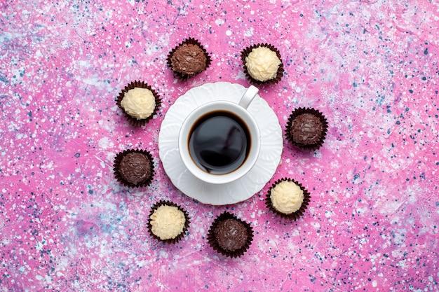 Vista superior de deliciosos caramelos de chocolate chocolate blanco y negro con taza de té en el escritorio rosa.