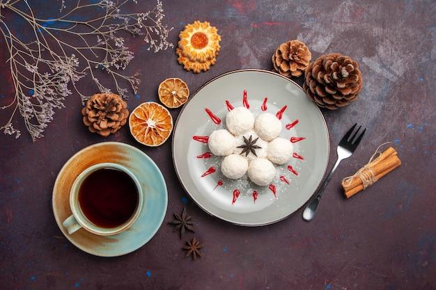 Vista superior de deliciosos caramelos de coco pequeños y redondos formados con una taza de té en el fondo oscuro, té de caramelo de coco, galleta de pastel dulce