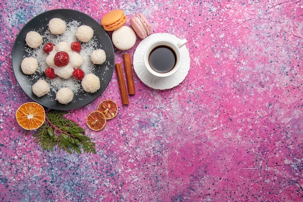 Vista superior de deliciosos caramelos de coco con taza de té en superficie rosa