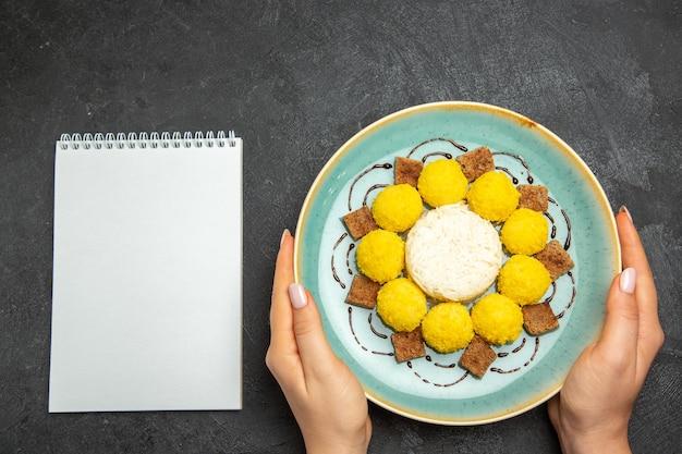 Vista superior de deliciosos caramelos dulces con pastel dentro de la placa sobre el fondo oscuro, galleta de té, pastel de caramelo dulce