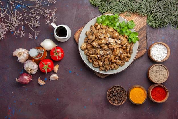 Vista superior deliciosos champiñones cocidos con condimentos y verduras sobre fondo oscuro plato de comida cena comida de plantas silvestres