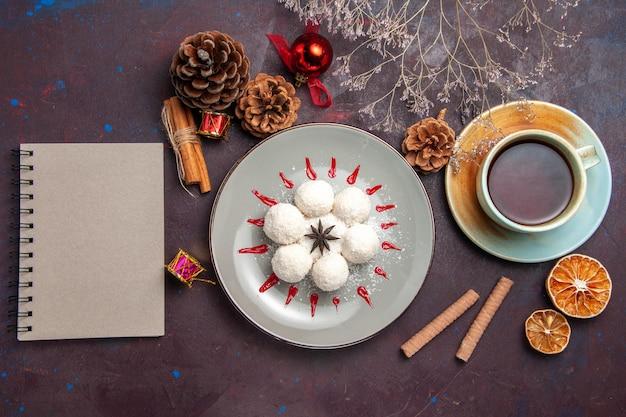 Vista superior de deliciosos dulces de coco con taza de té en negro