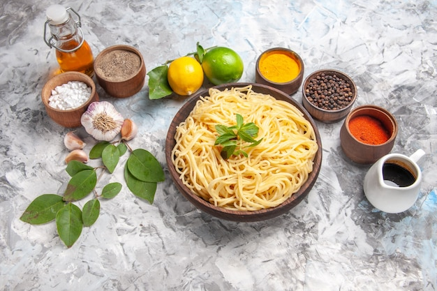Vista superior deliciosos espaguetis con condimentos en pasta de masa de comida de mesa blanca