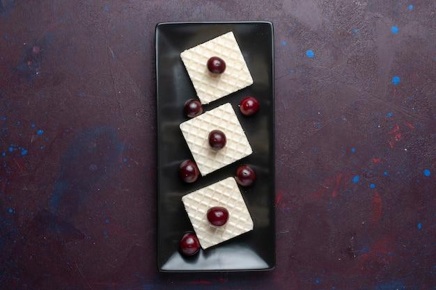 Vista superior de deliciosos gofres con cerezas dentro de la placa sobre la superficie oscura