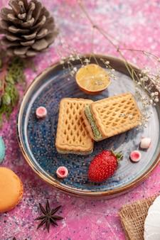 Vista superior de deliciosos gofres con macarons franceses en la superficie rosa