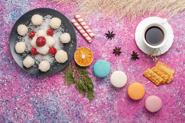 Vista superior de deliciosos macarons franceses con caramelos de coco y taza de té en superficie rosa