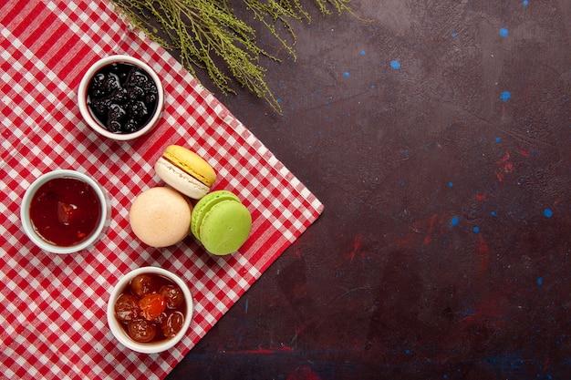 Vista superior deliciosos macarons franceses con mermeladas de frutas sobre fondo oscuro mermelada dulce té pastel galleta dulce