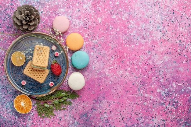 Vista superior de deliciosos macarons franceses con waffles en la superficie rosa