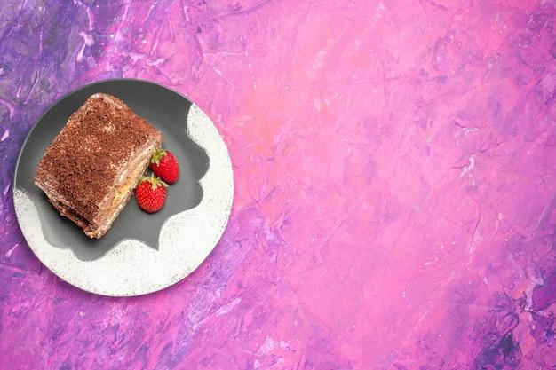 Vista superior de deliciosos panecillos dulces con fresas en superficie rosa