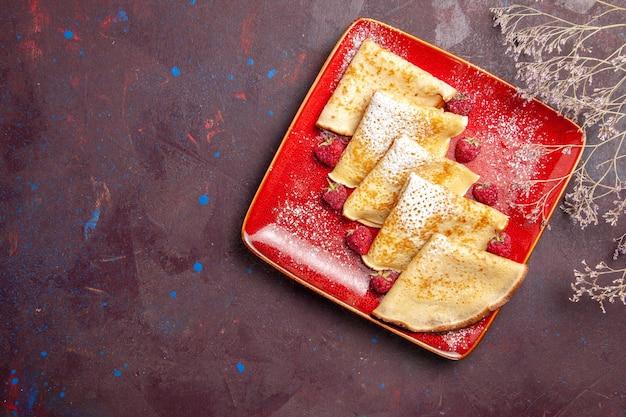Vista superior de deliciosos panqueques dulces dentro de la placa roja con frambuesas en negro