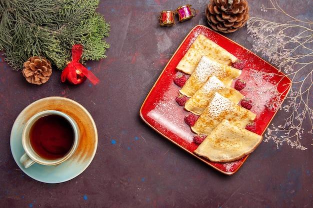 Vista superior de deliciosos panqueques dulces dentro de la placa roja con frambuesas en la oscuridad