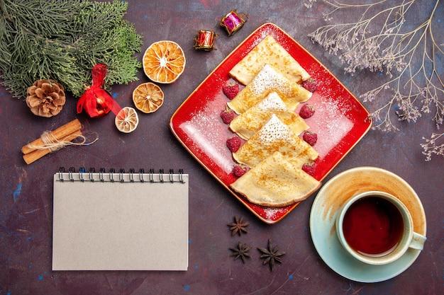 Vista superior de deliciosos panqueques dulces con frambuesas y taza de té en negro