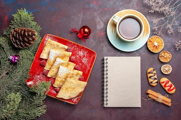Vista superior de deliciosos panqueques dulces con taza de té y frambuesas en negro