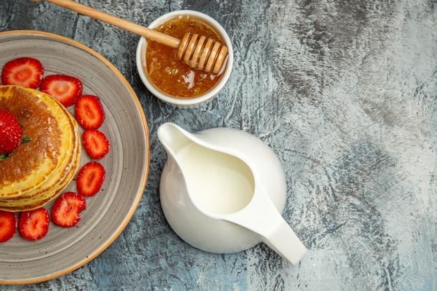 Vista superior deliciosos panqueques con frutas y miel a la luz