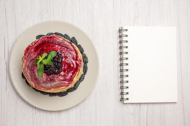 Vista superior deliciosos panqueques de gelatina con pasas y gelatina de frutas sobre fondo blanco mermelada de postre de galleta de gelatina dulce