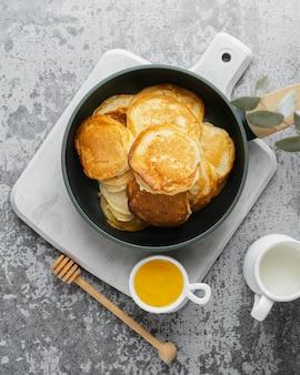 Vista superior deliciosos panqueques y miel.