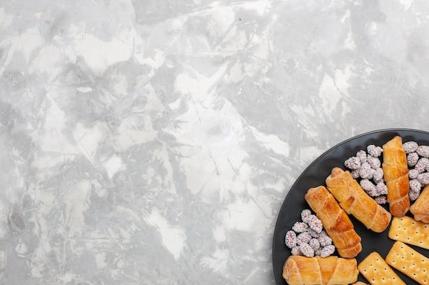 Vista superior de deliciosos pasteles con bagels y caramelos en la superficie blanca gris