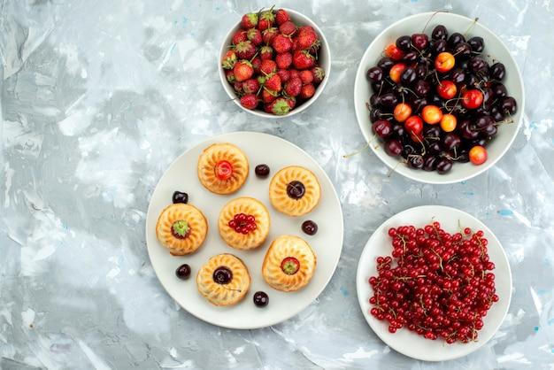 Una vista superior de deliciosos pasteles con bayas y frutas dentro de las placas pastel de azúcar de galleta